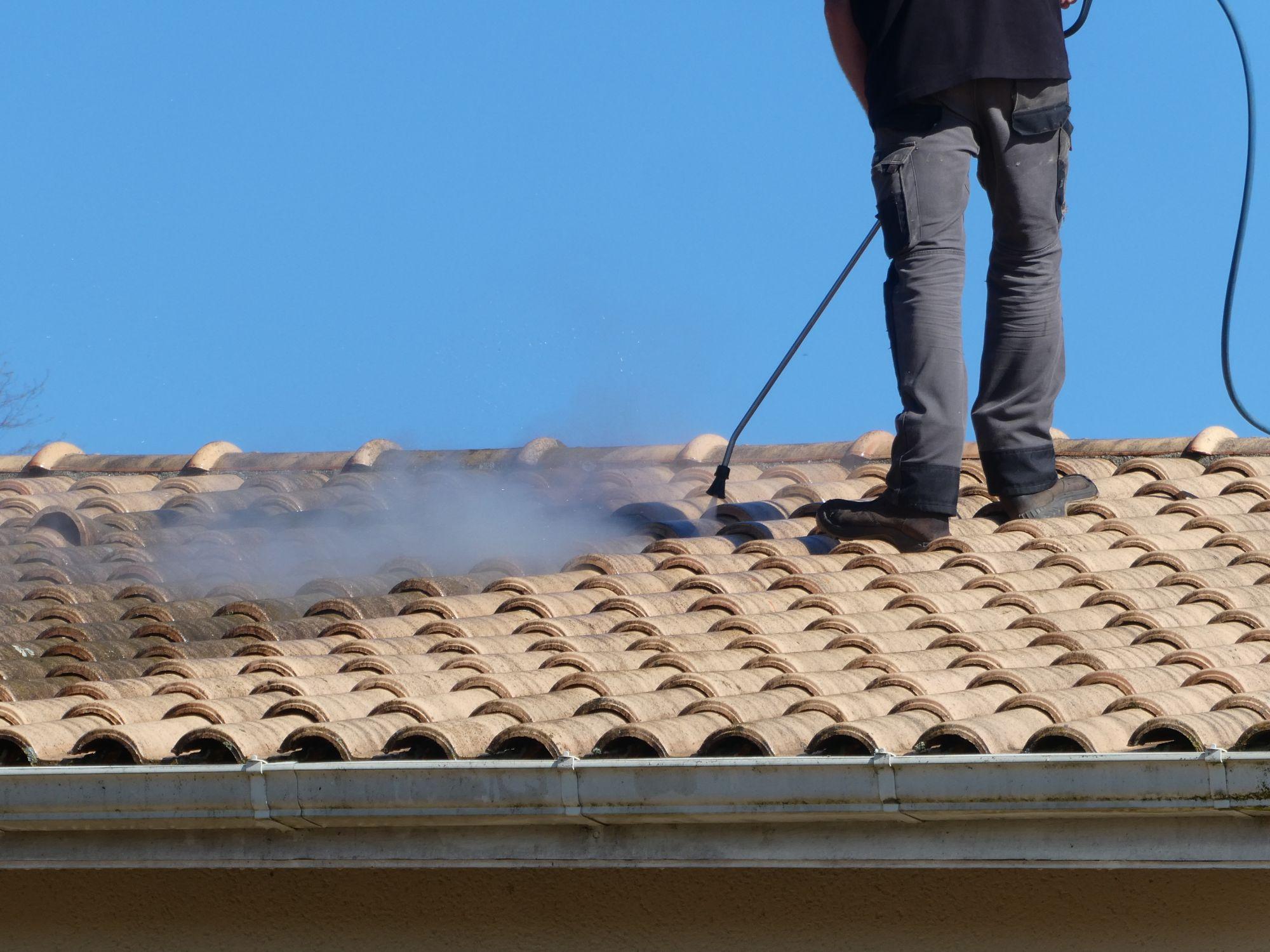 professionnel effectuant un nettoyage de toiture en haute ou basse pression